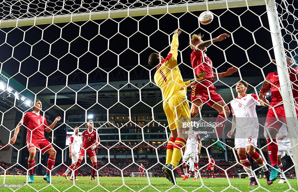 Goalkeeper Mladen Bozovic of Montenegro and Simon Kjar of Denmark compete for the ball during the FIFA World Cup 2018 european qualifier match between Denmark and Montenegro at Telia Parken Stadium on October 11, 2016 in Copenhagen, Denmark.