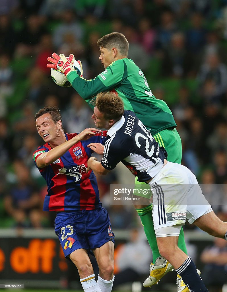 Goalkeeper Nathan Coe of the Victory makes a save as Nicholas Ansell of the Victory and Ryan Griffiths of the Jets compete for the ball during the...
