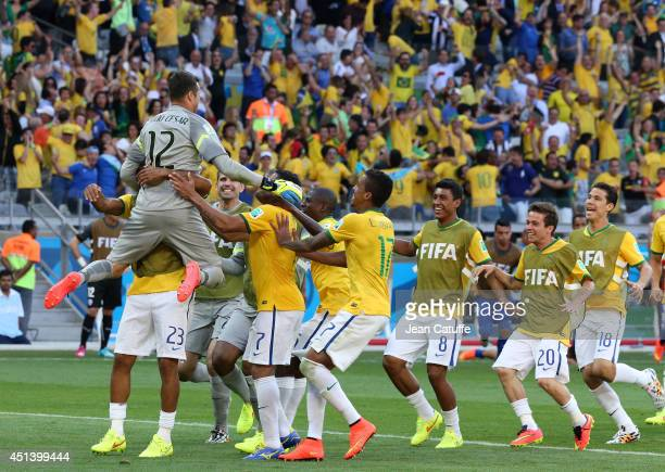 Goalkeeper of Brazil Julio Cesar is celebrated by his teammates after winning a penalty shootout during the 2014 FIFA World Cup Brazil round of 16...