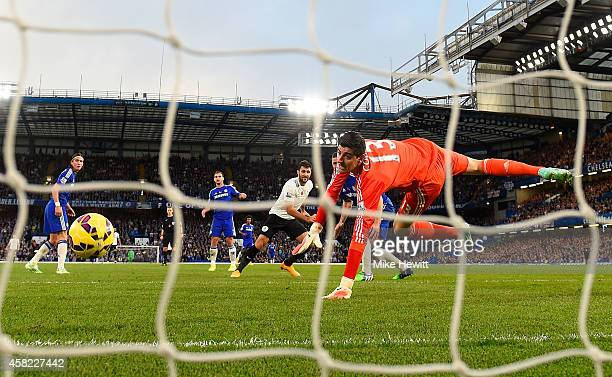Goalkeeper of Chelsea Thibaut Courtois fails to save a goal by Charlie Austin of Queens Park Rangers during the Barclays Premier League match between...