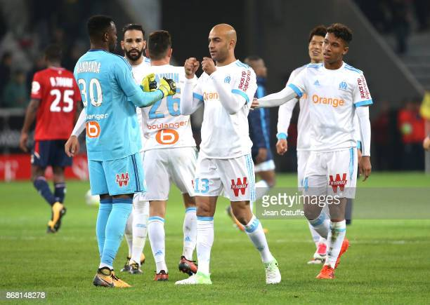 Goalkeeper of OM Steve Mandanda greets teammate Aymen Abdennour following the French Ligue 1 match between Lille OSC and Olympique de Marseille at...