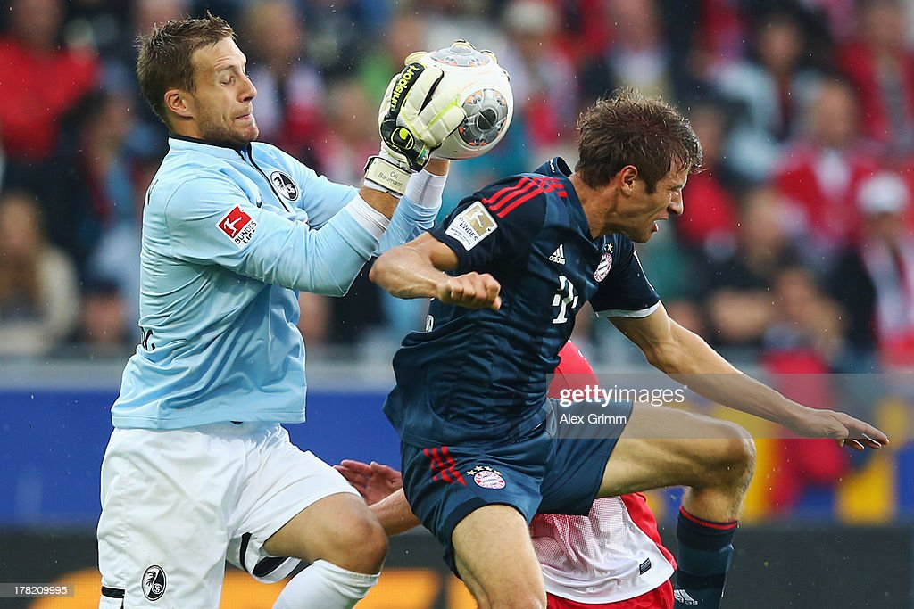 Goalkeeper Oliver Baumann of Freiburg catches the ball ahead of <a gi-track='captionPersonalityLinkClicked' href=/galleries/search?phrase=Thomas+Mueller&family=editorial&specificpeople=5842906 ng-click='$event.stopPropagation()'>Thomas Mueller</a> of Muenchen during the Bundesliga match between SC Freiburg and FC Bayern Muenchen at MAGE SOLAR Stadium on August 27, 2013 in Freiburg im Breisgau, Germany.