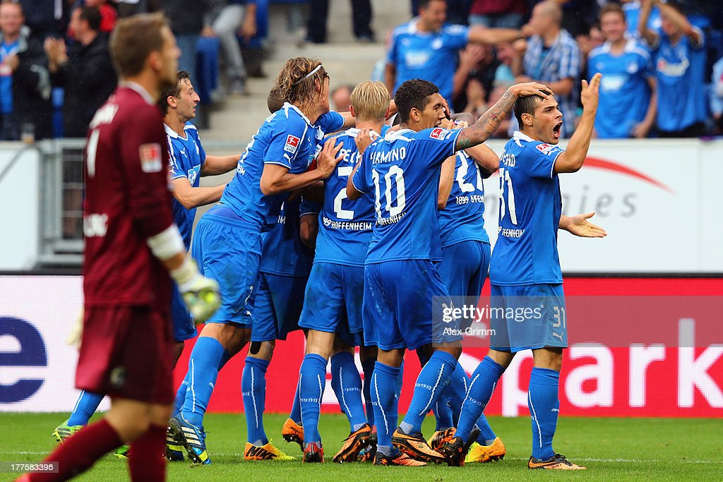 Goalkeeper Oliver Baumann (front) of Freiburg reacts as Tobias Strobl (hidden) of Hoffenheim celebrates his team's third goal with team mates during the Bundesliga match between 1899 Hoffenheim and SC Freiburg at Wirsol Rhein-Neckar-Arena on August 24, 2013 in Sinsheim, Germany.