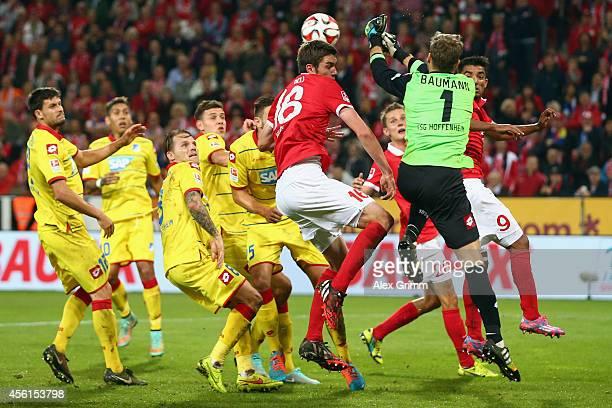 Goalkeeper Oliver Baumann of Hoffenheim is challenged by Stefan Bell of Mainz during the Bundesliga match between 1 FSV Mainz 05 and 1899 Hoffenheim...