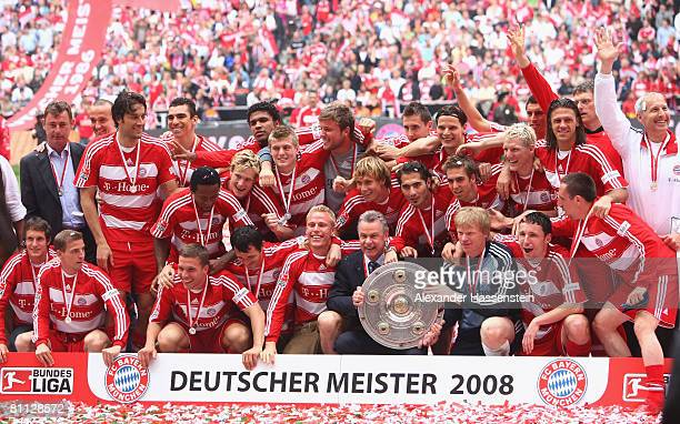 Goalkeeper Oliver Kahn and Munich's head coach Ottmar Hitzfeld and their team pose with the German Championship trophy after the Bundesliga match...