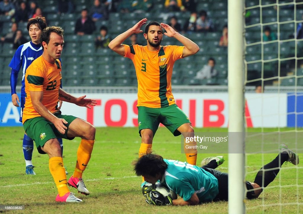 Goalkeeper Pan Wen Chieh of Chinese Tapei saves the ball at the feet of Ivan Franjic and Aziz Behich during the EAFF East Asian Cup 2013 Qualifying match between Chinese Tapei and the Australian Socceroos at Hong Kong Stadium on December 9, 2012 in So Kon Po, Hong Kong.
