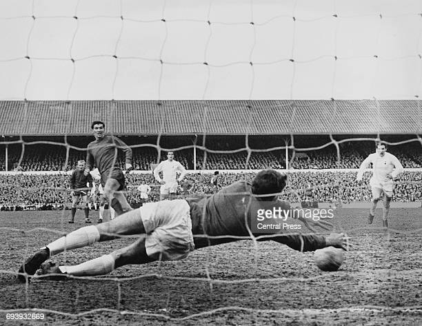Goalkeeper Pat Jennings of Spurs dives to save the penalty kick from Tony Ford of Bristol City as Alan Mullery and Mike England of Spurs look on...