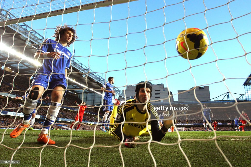 Goalkeeper <a gi-track='captionPersonalityLinkClicked' href=/galleries/search?phrase=Petr+Cech&family=editorial&specificpeople=212890 ng-click='$event.stopPropagation()'>Petr Cech</a> of Chelsea grasps at the ball as Martin Skrtel (not shown) of Liverpool scores the opening goal during the Barclays Premier League match between Chelsea and Liverpool at Stamford Bridge on December 29, 2013 in London, England.