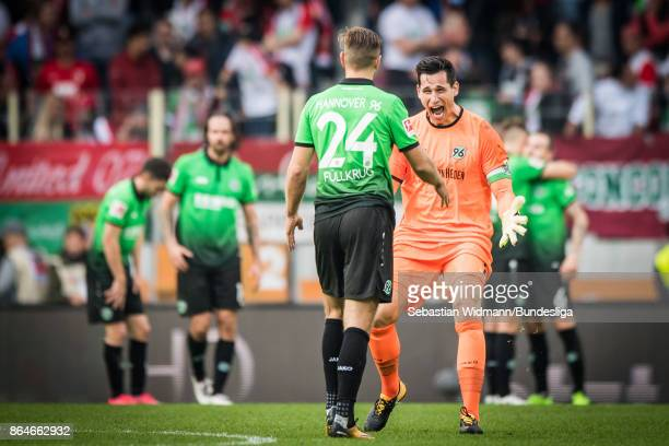 Goalkeeper Philipp Tschauner of Hannover 96 celebrates with teammate Florian Fuellkrug of Hannover 96 after the Bundesliga match between FC Augsburg...