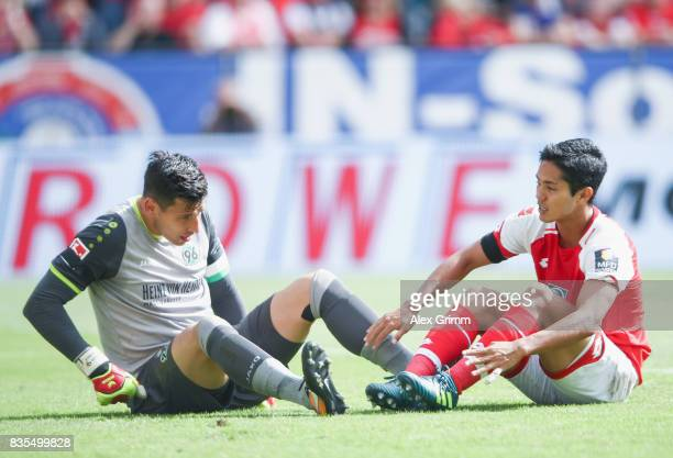 Goalkeeper Philipp Tschauner of Hannover and Yoshinori Muto of Mainz react during the Bundesliga match between 1 FSV Mainz 05 and Hannover 96 at Opel...