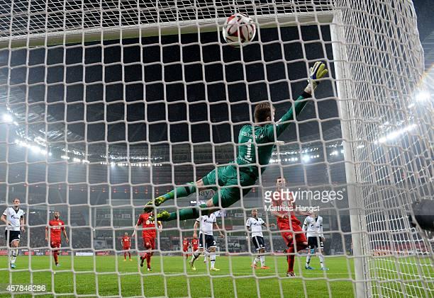 Goalkeeper Ralf Faehrmann of Schalke dives in vain as Hakan Calhanoglu of Bayer Leverkusen scores the only goal of the game during the Bundesliga...