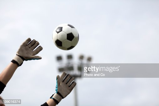 Goalkeeper reaching for ball : Stock Photo