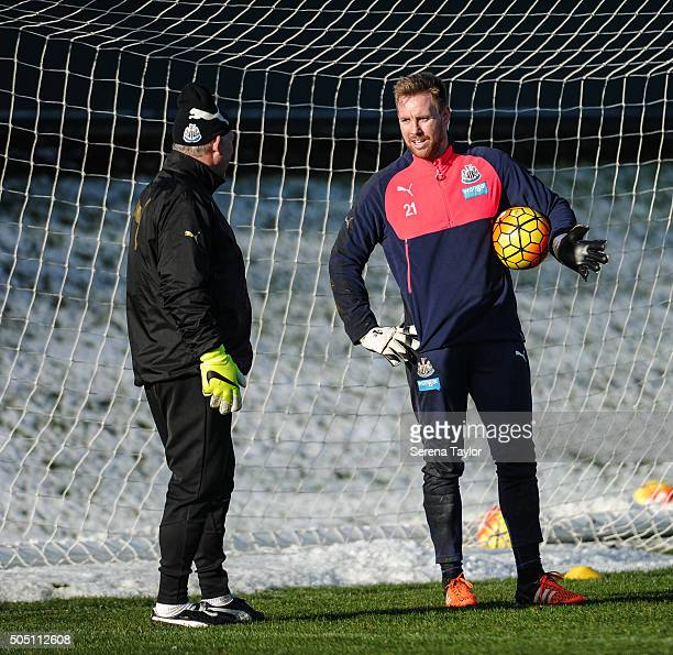 Goalkeeper Rob Elliot holds the ball under his arm whilst talking to Goalkeeping coach Simon Smith during the Newcastle United Training session at...