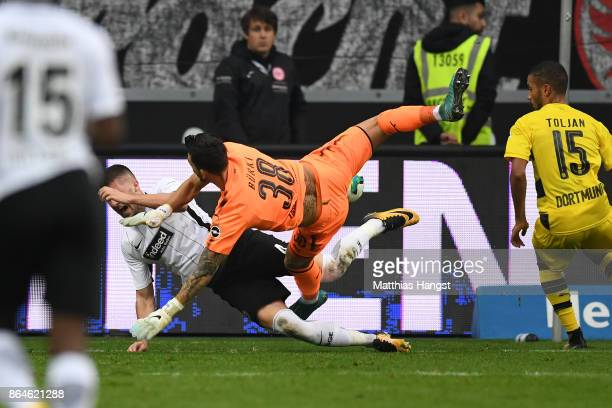 Goalkeeper Roman Buerki of Dortmund fouls Ante Rebic of Frankfurt which results in a penalty for Frankfurt during the Bundesliga match between...