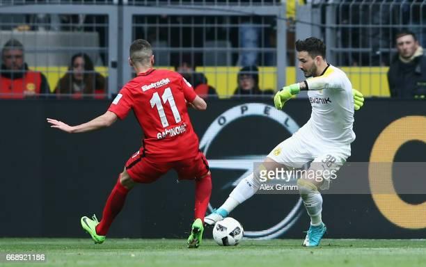 Goalkeeper Roman Buerki of Dortmund is challenged by Mijat Gacinovic of Frankfurt during the Bundesliga match between Borussia Dortmund and Eintracht...