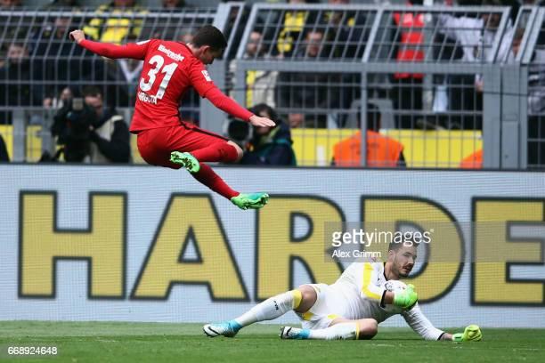 Goalkeeper Roman Buerki of Dortmund makes a save ahead of Branimir Hrgota of Frankfurt during the Bundesliga match between Borussia Dortmund and...