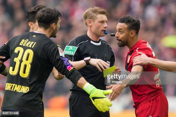 Goalkeeper Roman Buerki of Dortmund Referee Christian Dingert and Karim Bellarabi of Bayer Leverkusen during the Bundesliga match between Borussia...