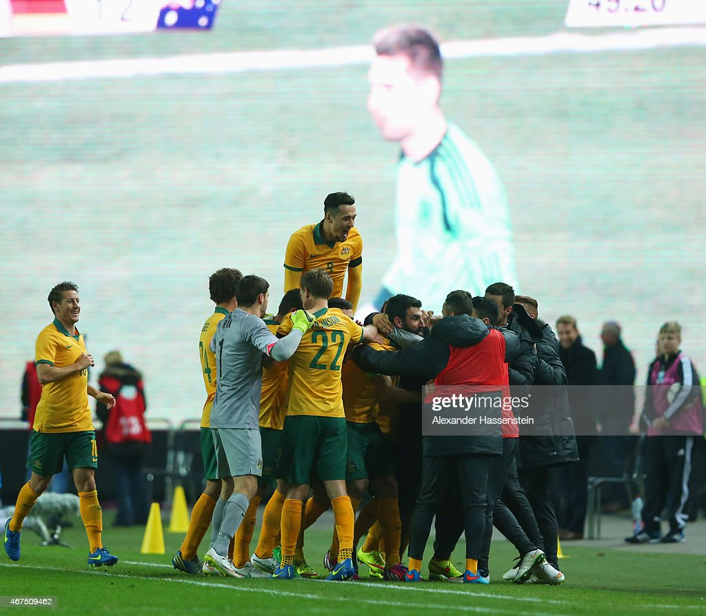 Goalkeeper RonRobert Zieler of Germany is shown on the scoreboard as Mile Jedinak of Australia celebrates with team mates as he scores their second...