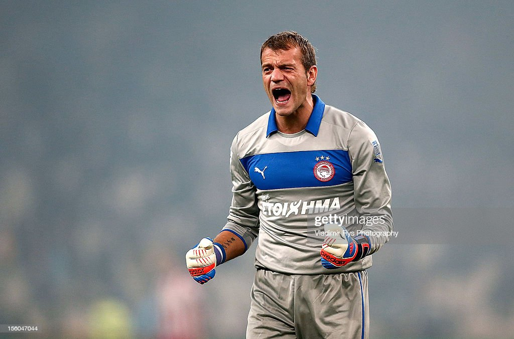 Goalkeeper <a gi-track='captionPersonalityLinkClicked' href=/galleries/search?phrase=Roy+Carroll&family=editorial&specificpeople=206286 ng-click='$event.stopPropagation()'>Roy Carroll</a> of Olympiacos celebrates after his team's third goal is scored by team-mate Kostas Mitroglou, during the Superleague match between AEK Athens and Olympiacos Piraeus at OAKA Stadium on November 11, 2012 in Athens, Greece.