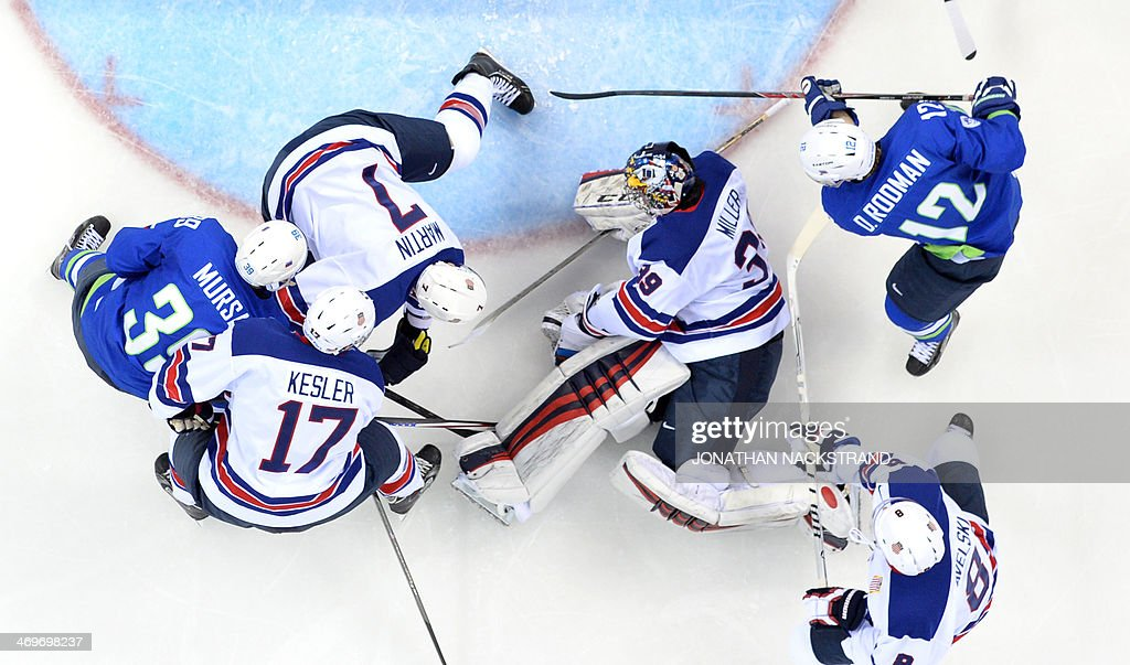 US goalkeeper Ryan Miller (C) dives for the puck during the Men's Ice Hockey Group A match between Slovenia and USA at the Shayba Arena during the Sochi Winter Olympics on February 16, 2014.