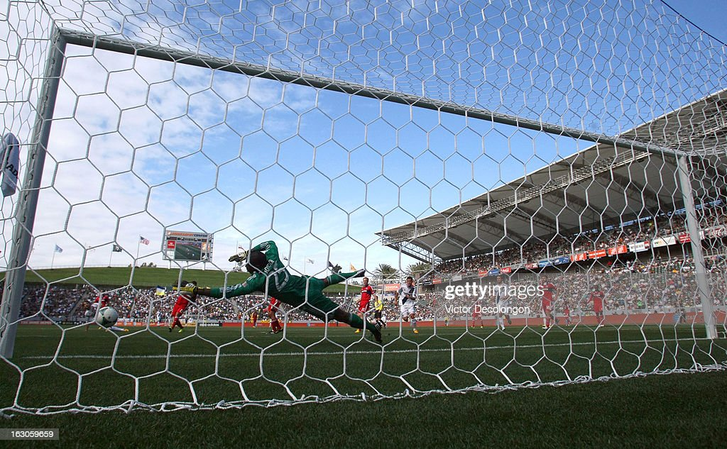 Goalkeeper Sean Johnson of the Chicago Fire can't make the save as Colin Clark and Todd Dunivant of the Los Angeles Galaxy watch the ball go into the...