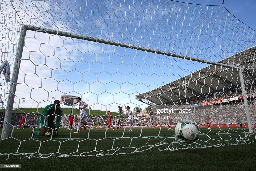 Goalkeeper Sean Johnson of the Chicago Fire watches the ball in the net as Colin Clark and Todd Dunivant of the Los Angeles Galaxy react to the goal...