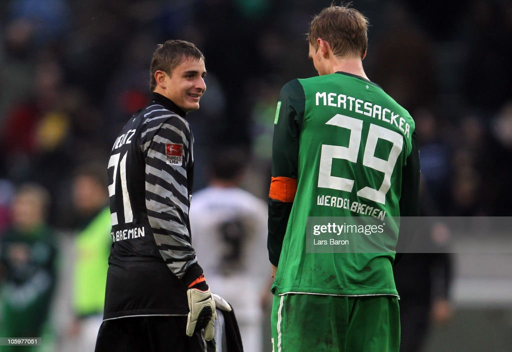 Goalkeeper Sebastian Mielitz of Bremen smiles with team mate <a gi-track='captionPersonalityLinkClicked' href=/galleries/search?phrase=Per+Mertesacker&family=editorial&specificpeople=207135 ng-click='$event.stopPropagation()'>Per Mertesacker</a> after winning the Bundesliga match between Borussia Moenchengladbach and Werder Bremen at Borussia Park Stadium on October 23, 2010 in Moenchengladbach, Germany.