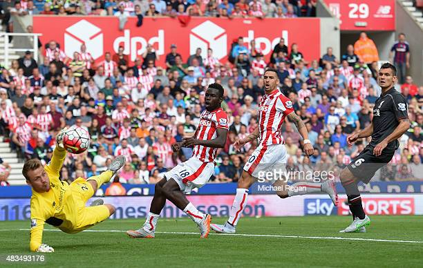 Goalkeeper Simon Mignolet of Liverpool dives for the ball as Mame Biram Diouf and Geoff Cameron of Stoke City and Dejan Lovren of Liverpool look on...