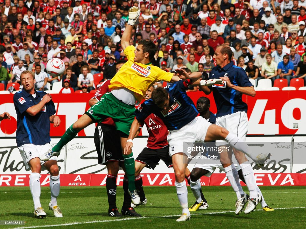 Goalkeeper <a gi-track='captionPersonalityLinkClicked' href=/galleries/search?phrase=Simon+Pouplin&family=editorial&specificpeople=2087398 ng-click='$event.stopPropagation()'>Simon Pouplin</a> (2ndL) of Freiburg misses to save a ball during the Bundesliga match between 1. FC Nuernberg and SC Freiburg at Easy Credit stadium on August 28, 2010 in Nuremberg, Germany.
