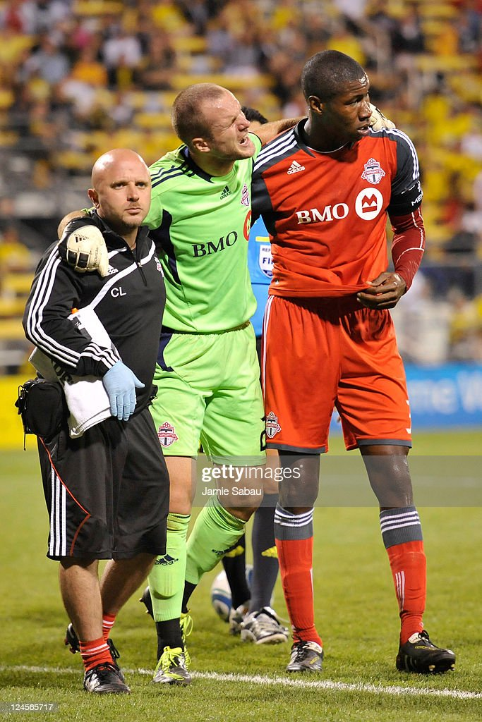 Goalkeeper Stefan Frei #24 of Toronto FC is helped off the field by a trainer and Andy Iro #3 of Toronto FC after being injured in a collision with a Columbus Crew player on September 10, 2011 at Crew Stadium in Columbus, Ohio. Toronto FC defeated Columbus 4-2 to take the Trillium Cup for the first time.