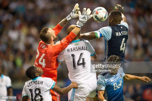 goalkeeper Stefan Frei Seattle Sounders defender Chad Marshall and Vancouver Whitecaps defender Kendall Waston jump for the ball during their match...