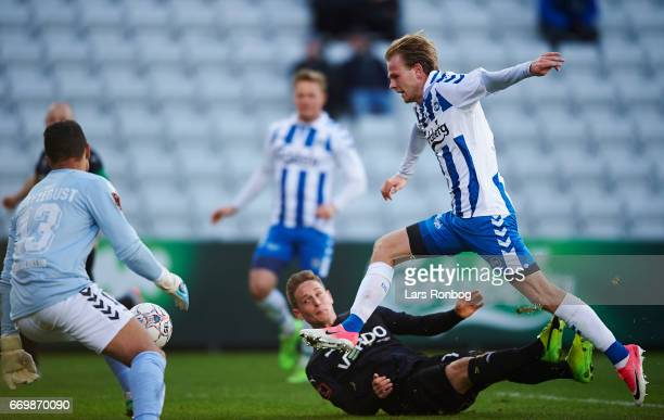 Goalkeeper Sten Grytebust of OB Odense Andreas Bruhn of Randers FC and Mikkel Desler of OB Odense compete for the ball during the Danish Alka...