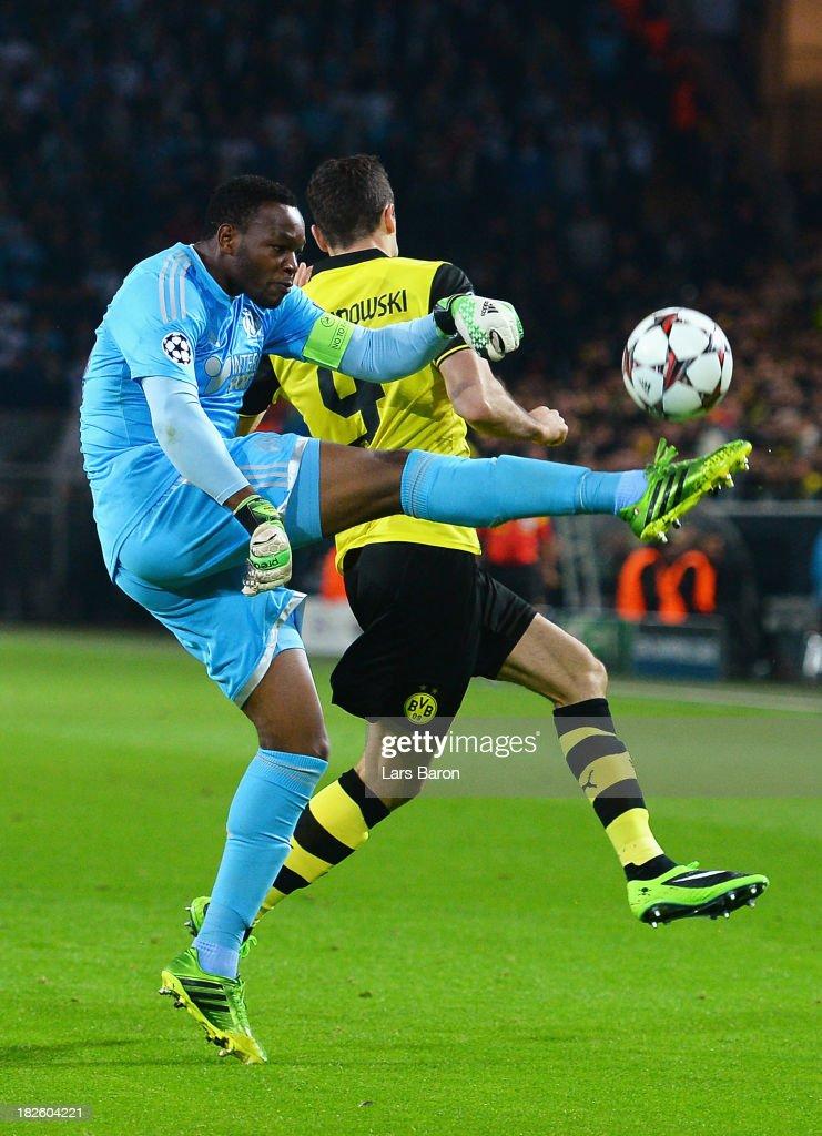 Goalkeeper Steve Mandanda of Olympique Marseille clears past Robert Lewandowski of Borussia Dortmund during the UEFA Champions League Group F match...