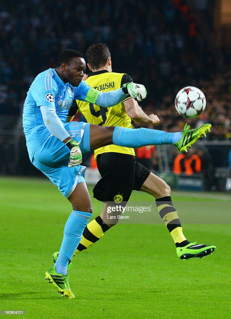 Goalkeeper Steve Mandanda of Olympique Marseille clears past Robert Lewandowski of Borussia Dortmund during the UEFA Champions League Group F match between Borussia Dortmund and Olympique de Marseille at Signal Iduna Park on October 1, 2013 in Dortmund, Germany.