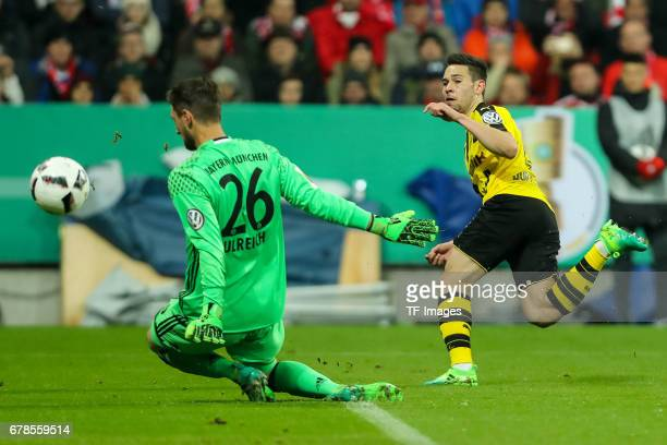 Goalkeeper Sven Ulreich of Bayern Munich and Raphael Guerreiro of Dortmund battle for the ball during the German Cup semi final soccer match between...