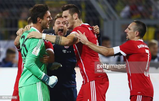 Goalkeeper Sven Ulreich of Muenchen celebrates with team mates Niklas Suele and Franck Ribery after the penalty shootout of the DFL Supercup 2017...