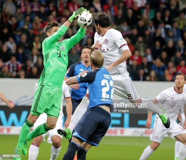 Goalkeeper Sven Ulreich of Munich and Kevin Vogt of Hoffenheim and Javi Martínez of Munich battle for the ball during the Bundesliga match between...