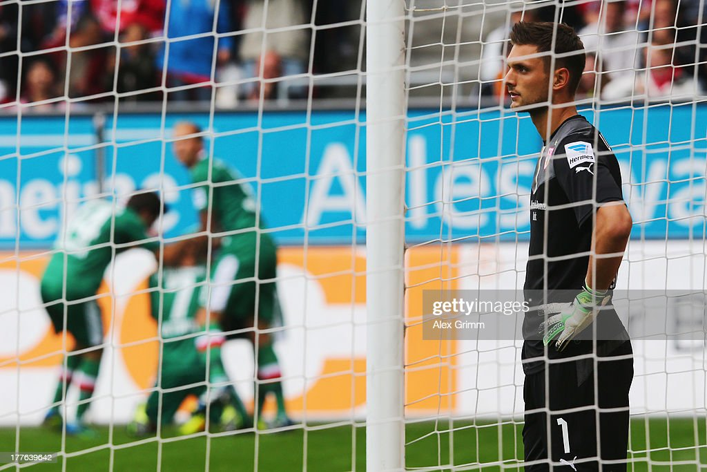 Goalkeeper Sven Ulreich of Stuttgart reacts as Halil Altintop (back) of Augsburg celebrates his team's first goal with team mates during the Bundesliga match between FC Augsburg and VfB Stuttgart at SGL Arena on August 25, 2013 in Augsburg, Germany.