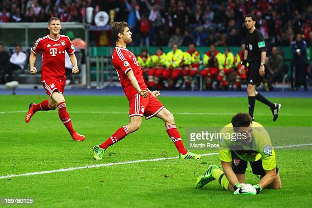 Goalkeeper Sven Ulreich of VfB Stuttgart looks dejected as Thomas Mueller of Bayern Muenchen celebrates scoring their first goal from the penalty...