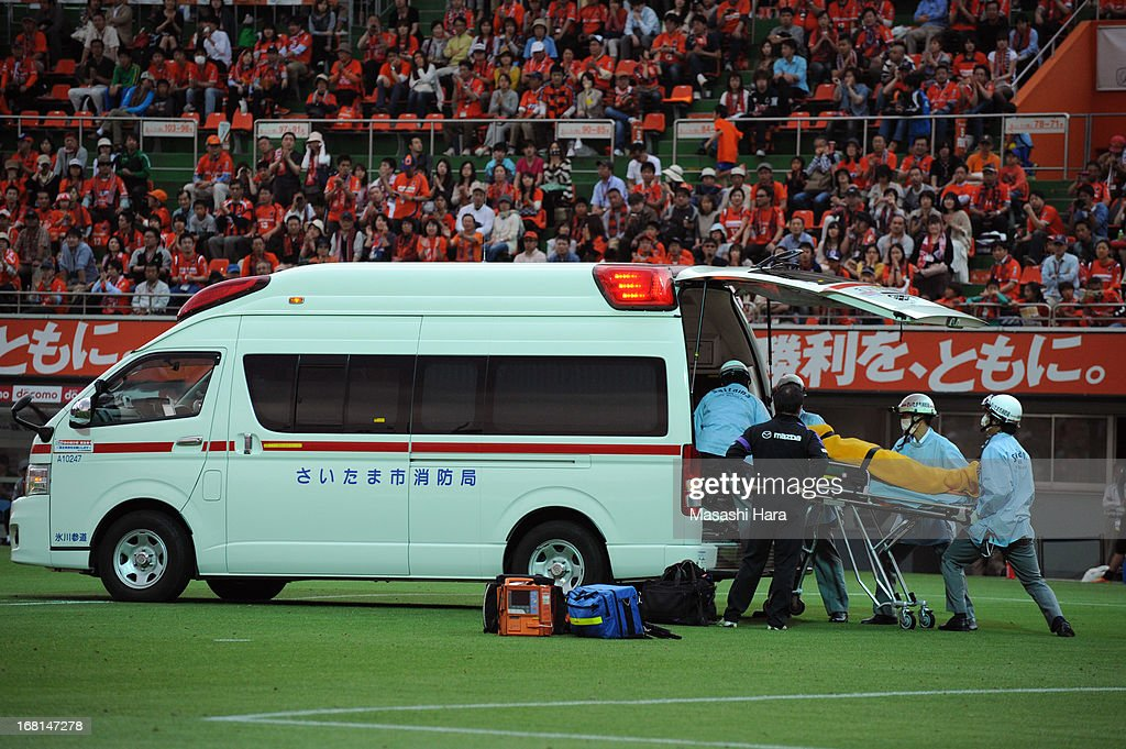 Goalkeeper Takuya Masuda #13 of Sanfrecce Hiroshima is carried into an ambulance on a stretcher after colliding with Takamitsu Tomiyama #28 of Omiya Ardija, who scored the second goal, during the J.League match between Omiya Ardija and Sanfrecce Hiroshima at Nack 5 Stadium Omiya on May 6, 2013 in Saitama, Japan.