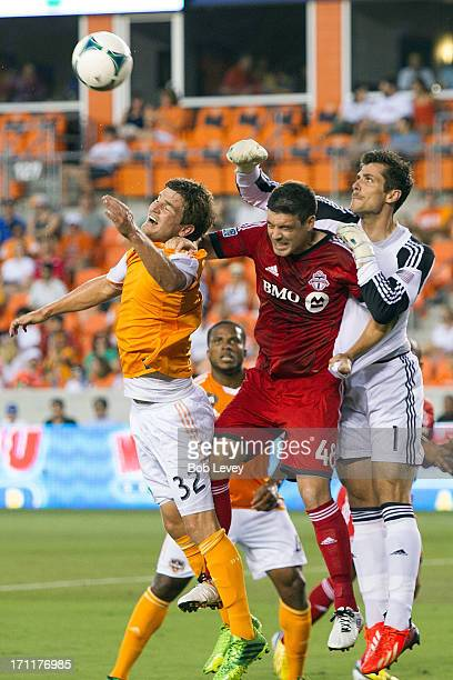 Goalkeeper Tally Hall of Houston Dynamo goes over the top of Darren O'Dea of Toronto FC and Bobby Boswell of Houston Dynamo to clear the ball at BBVA...