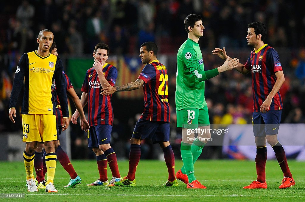 Goalkeeper Thibaut Courtois of Club Atletico de Madrid shakes hands with Sergio Busquets of Barcelona as Lionel Messi of Barcelona grimaces after the UEFA Champions League Quarter Final first leg match between FC Barcelona and Club Atletico de Madrid at Camp Nou on April 1, 2014 in Barcelona, Spain.