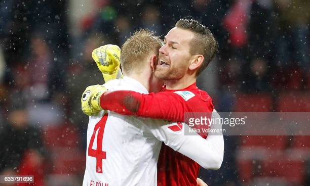 Goalkeeper Thomas Kessler of Cologne celebrates the victory 10 with Frederik Soerensen of Cologne during the Bundesliga match between 1 FC Koeln and...