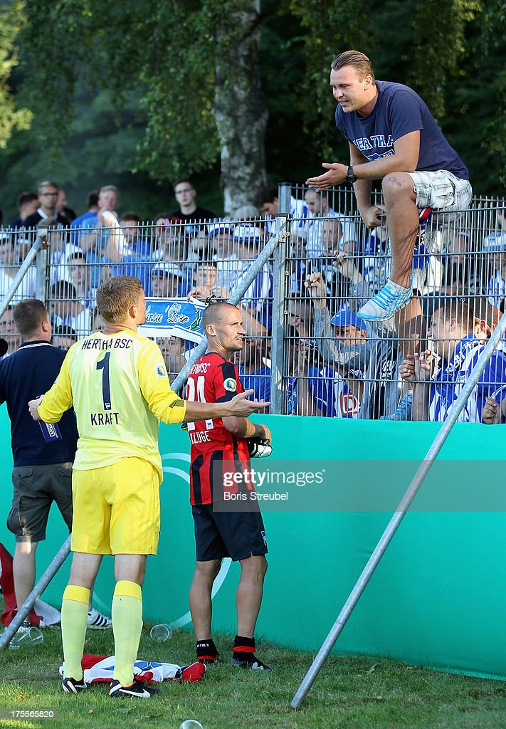 Goalkeeper Thomas Kraft (L) and <a gi-track='captionPersonalityLinkClicked' href=/galleries/search?phrase=Peer+Kluge&family=editorial&specificpeople=635201 ng-click='$event.stopPropagation()'>Peer Kluge</a> (C) of Hertha BSC talk to upset fans after the DFB Cup first round match between VfR Neumuenster and Hertha BSC Berlin at Gruemmi-Arena on August 4, 2013 in Neumuenster, Germany.