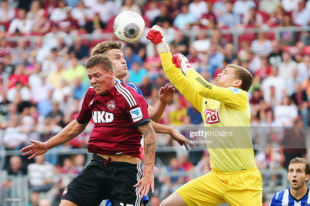 Goalkeeper Thomas Kraft of Berlin clears the ball ahead of <a gi-track='captionPersonalityLinkClicked' href=/galleries/search?phrase=Mike+Frantz&family=editorial&specificpeople=5633011 ng-click='$event.stopPropagation()'>Mike Frantz</a> of Nuernberg during the Bundesliga match between 1. FC Nuernberg and Hertha BSC Berlin at Grundig Stadium on August 18, 2013 in Nuremberg, Germany.