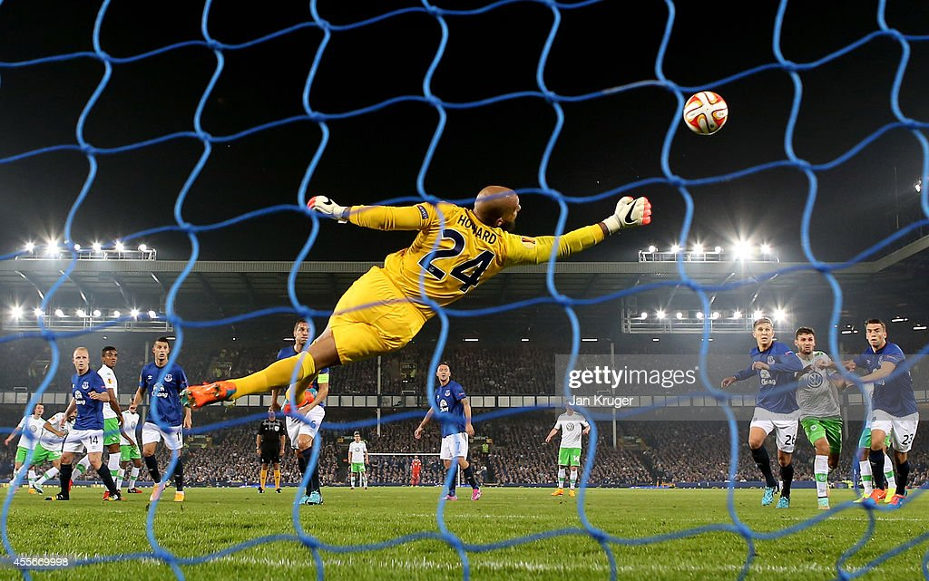 Goalkeeper Tim Howard of Everton dives in vain as Ricardo Rodríguez (2nd L - obscured) of VfL Wolfsburg scores a late consolation goal during the UEFA Europa League Group H match between Everton and VFL Wolfsburg on September 18, 2014 in Liverpool, United Kingdom.