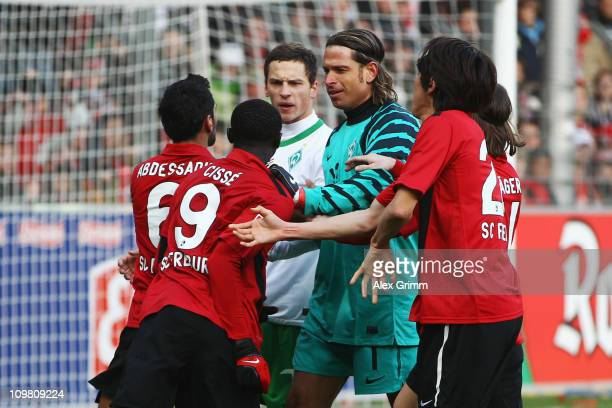 Goalkeeper Tim Wiese and Marko Arnautovic of Bremen argue with Yacine Abdessadki and Papiss Demba Cisse of Freiburg during the Bundesliga match...