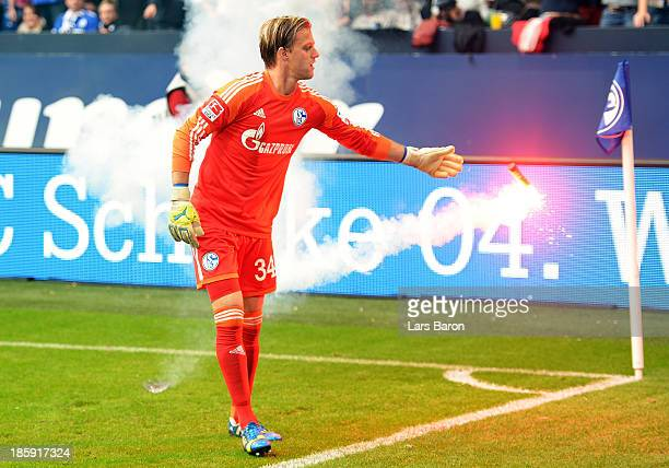 Goalkeeper Timo Hildbrand of Schalke takes a flare from the pitch during the Bundesliga match between FC Schalke 04 and Borussia Dortmund at...