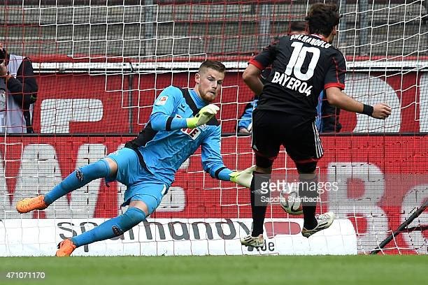 Goalkeeper Timo Horn of Koeln saves the ball from a penalty of Hakan Calhanoglu of Leverkusen during the Bundesliga match between 1 FC Koeln and...