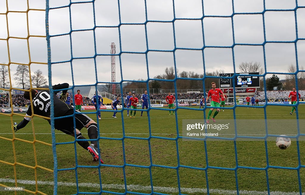 Goalkeeper Tino Berbig of Jena without a chance, Nico Hammann of Magdeburg scores the opening goal / Penaltykick during the Regionalliga match between FC Carl Zeiss Jena and 1.FC Magdeburg at Ernst Abbe Sportfeld on March 16, 2014 in Jena, Germany.